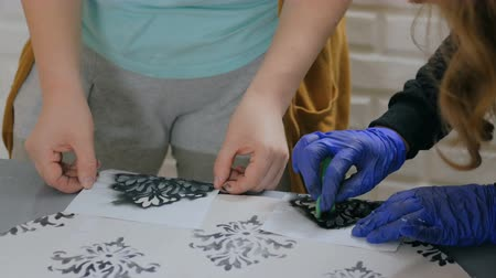decorador : Stencil painting concept: close up shot of woman hands painting on wooden circle