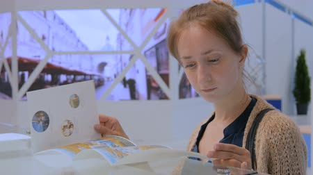 буклет : Woman reading advertisement brochure at urban exhibition