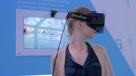 захват : MOSCOW, RUSSIA - JULY 12, 2017: Moscow Urban Forum. Young woman using virtual reality headset and watching interactive presentation. VR and future concept