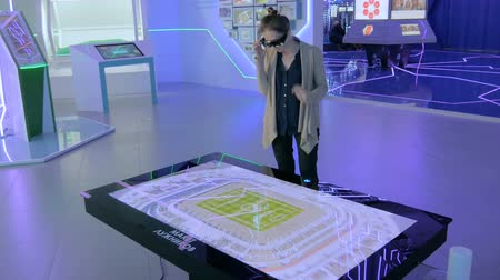 interactive table : MOSCOW, RUSSIA - August 10, 2017: Smart City Exhibition. Augmented reality experience: woman using special glasses, looking at display table with 3d virtual hologram maquette of stadium Luzhniki Stock Footage