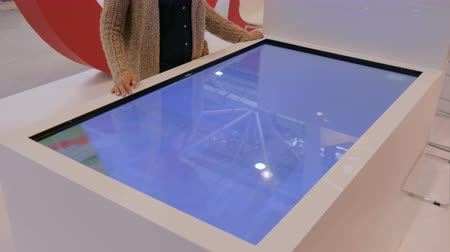 interactive table : MOSCOW, RUSSIA - JULY 12, 2017: Moscow Urban Forum. Woman using interactive touchscreen display table at urban exhibition - scrolling and touching