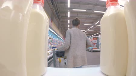 hűtőgép : Woman buying fresh milk at grocery store. Point of view shot. Consumerism, sale, shopping and health care concept