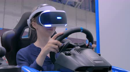 invisible : NIZHNIY NOVGOROD, RUSSIA - August 7, 2017: The Exhibition Park Of Robots. Young woman using virtual reality headset and playing in car drive simulator at technology exhibition. Video game concept
