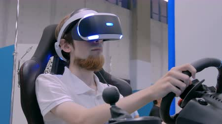 playstation : NIZHNIY NOVGOROD, RUSSIA - August 7, 2017: The Exhibition Park Of Robots. Young man using virtual reality headset and playing in car drive simulator at technology exhibition. Video game concept Stock Footage