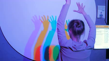 polychrome : Interactive exposition in science museum. Colored shadows of dancing woman. Science, optical and physics concept