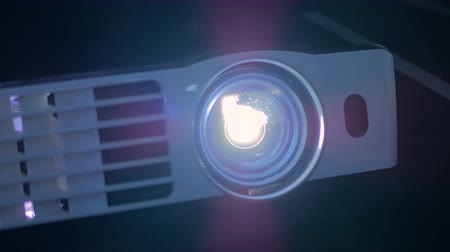 prezentaci : Front view of digital film projector, lens flare. Cinema and entertainment concept