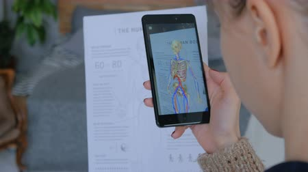 fyziologie : MOSCOW, RUSSIA - FEBRUARY 10, 2018. Woman using smartphone with augmented reality app - educational anatomy human body system. Future, medical and technology concept
