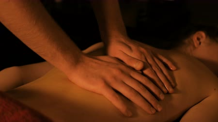 profesyonel meslek : Professional male masseur doing massage for female client at spa salon, studio. Warm romantic illumination, low key. Pleasure, healthcare, beauty and relaxation concept