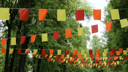 árbocszalag : Decorative garlands of red, yellow and orange rectangular flags on street between trees