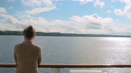 kruvazör : Young woman standing on deck of cruise ship and looking at river and landscape. Relax, nature and journey concept Stok Video