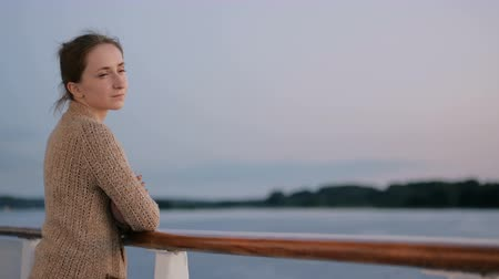 wistful : Woman standing on deck of cruise ship and looking at landscape after sunset. Relax, nature and journey concept