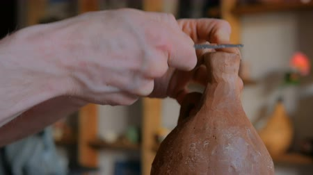 louça de barro : Professional male potter shaping and scraping dry clay jar with special tool in pottery workshop, studio. Crafting, artwork and handmade concept