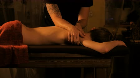 массаж : Young woman enjoying massage in spa salon with warm romantic illumination. Body care, beauty and harmony concept