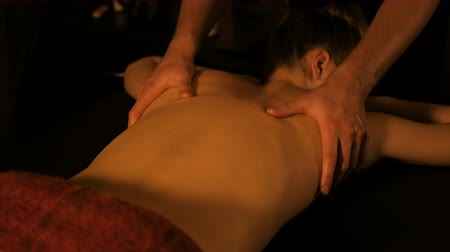 rozmazlování : Professional male masseur doing back massage for female client in spa center, studio. Wellness, harmony, relaxation and healthcare concept