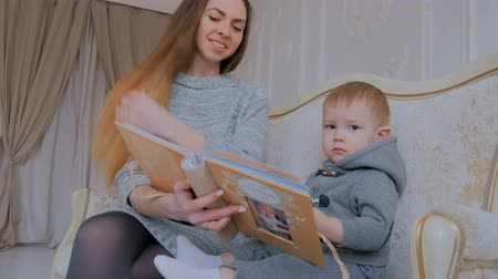 photo album : Young mother and her baby son looking photobook togerher at home. Family, childhood and leisure concept