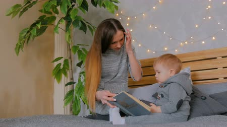 alfabetização : Young mother and her baby son reading book togerher at home. Family, childhood and leisure concept
