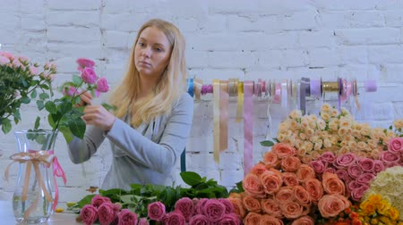 kwiaciarnia : Professional floral artist, florist cutting flowers - pink roses at flower shop, workshop. Floristry, handmade and artwork concept