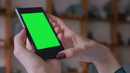oleiro : Woman looking at vertical smart phone with green screen in pottery workshop, studio. Close up shot of woman hands with mobile phone