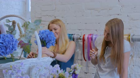 decorador : Two professional women floral artists, florists making large floral basket with flowers at workshop, flower shop. Floristry, handmade and small business concept