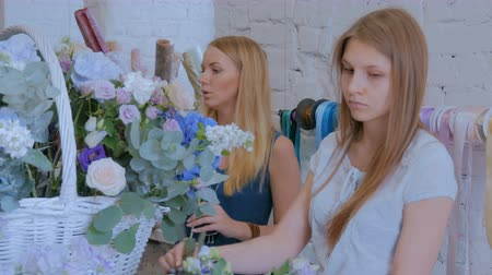 dekoratör : Two professional women floral artists, florists making large floral basket with flowers at workshop, flower shop. Floristry, handmade and small business concept