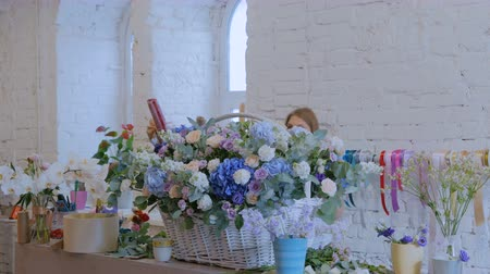 arranging : Two professional women floral artists, florists making large floral basket with flowers at workshop, flower shop. Floristry, handmade and small business concept