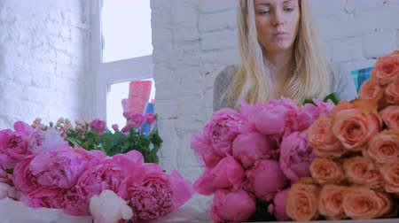 decorador : Professional floral artist, florist sorting flowers - pink peonies for bouquet at workshop, flower shop. Floristry, handmade and small business concept Stock Footage