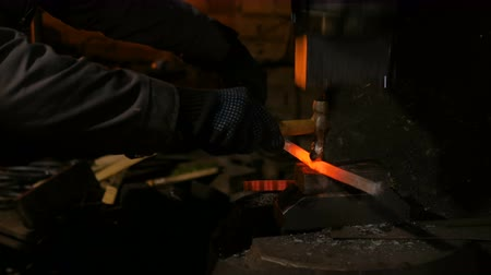 навыки : Professional blacksmith using hammer machine and forging molten metal at smithy, workshop. Handmade, craftsmanship and blacksmithing concept