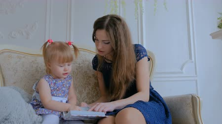 photo album : Young mother and her baby daughter looking photobook togerher at home. Family, childhood and leisure concept