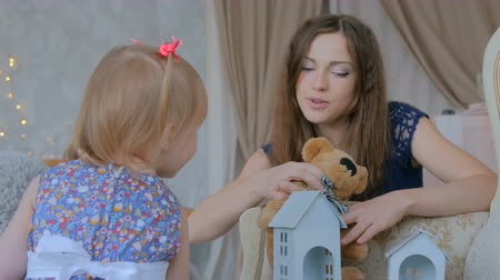 плюшевый мишка : 2 shots. Young mother and her baby daughter playing togerher at home. Family, childhood and leisure concept