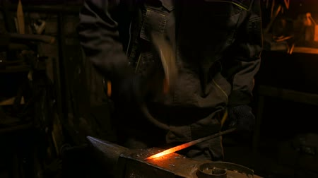 Professional blacksmith working with metal on anvil at forge, workshop. Handmade, craftsmanship and blacksmithing concept