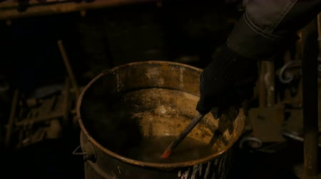 Professional blacksmith working with metal - quenching hot iron part of forged gate in water at forge, workshop. Handmade, craftsmanship and blacksmithing concept Wideo