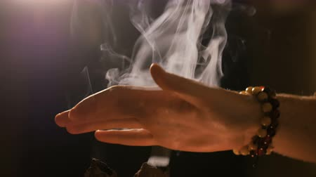 Smoke from incense rises through man fingers. Warm romantic illumination, low key. Relaxation, meditative and aromatherapy concept