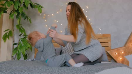 Young mother and her baby son playing togerher at home. Family, childhood and leisure concept