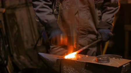 Professional blacksmith forging molten metal on anvil at smithy, workshop. Handmade, craftsmanship and blacksmithing concept