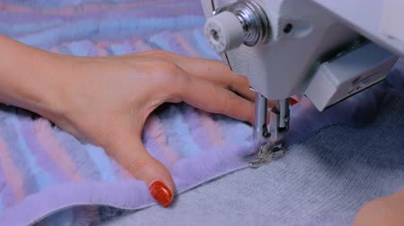 Close up shot - professional tailor, fashion designer sewing colorful fur coat with sewing machine at atelier, studio. Fashion and tailoring concept Wideo
