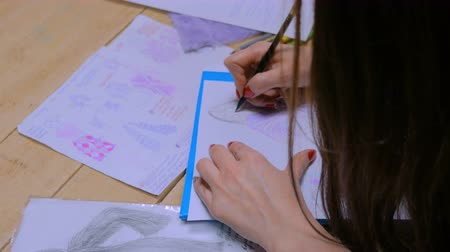 Close up shot - hands of professional tailor, designer drawing fashion sketch at atelier, studio. Dressmaking, creativity and tailoring concept