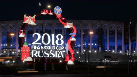 korkuluk : NIZHNIY NOVGOROD, RUSSIA - JUNE 2018: Official logo board construction FIFA World Cup 2018 on city street with traffic at night - time lapse shot