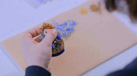 aninhada : Professional jewelry designer making handmade brooch in traditional russian style with beads in studio, workshop. Traditional, creativity, folklore and handmade concept