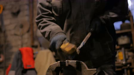 Professional blacksmith working with metal at forge, workshop. Handmade, craftsmanship and blacksmithing concept