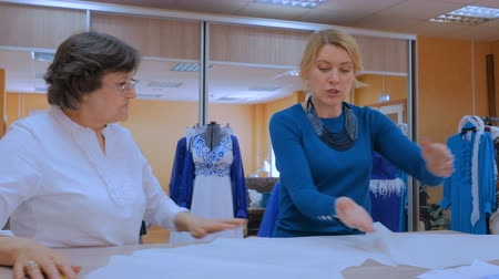 couture : Two professional women tailors, designers discussing pattern of new couture collection at atelier, studio. Dressmaking, creativity and tailoring concept