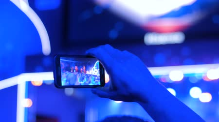 make photo : Unrecognizable hands silhouette taking photo or recording video of live music concert with smartphone. Photography, entertainment and technology concept