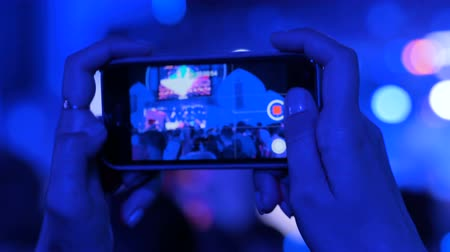 rock festival : Unrecognizable hands silhouette taking photo or recording video of live music concert with smartphone. Photography, entertainment and technology concept
