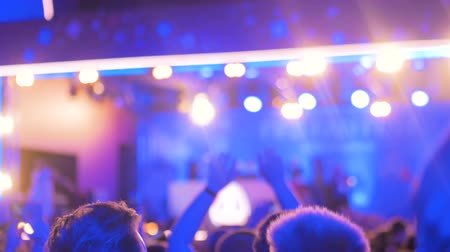 hayranlık : Abstract defocused concert background - people partying at night open air in front of the stage. Nightlife and entertainment concept Stok Video
