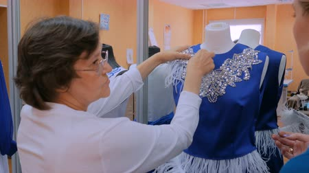 material body : Two professional tailors, designers working with new model tailoring dress on mannequin in studio, atelier. Fashion and tailoring concept Stock Footage