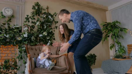 łaskotki : Happy young parents and their baby daughter playing togerher at home. Family, childhood and leisure concept