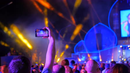 zenekar : Unrecognizable man hands silhouette taking photo or recording video of live music concert with smartphone at night. Photography, entertainment and technology concept