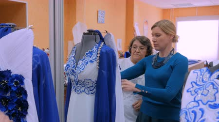 dressmakers model : Two professional tailors, designers working with new model tailoring dress on mannequin in studio, atelier. Fashion and tailoring concept Stock Footage