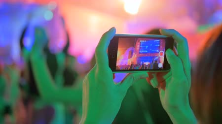 concert crowd : Unrecognizable hands silhouette taking photo or recording video of live music concert with smartphone at night. Photography, entertainment and technology concept