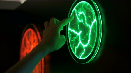 electrostatic : Interactive exposition in science museum. Woman touching plasma panel display. Electricity and physics concept
