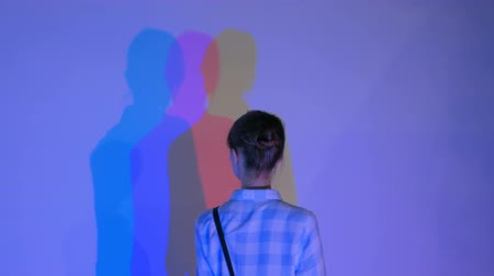 polychrome : Interactive exposition in science museum. Colored shadows of woman. Science, optical and physics concept